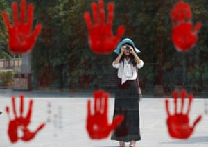 A visitor takes a picture of a display bearing hand prints of war heroes from the War of Resistance against Japan