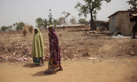 Two women walk past the archaeological excavation site where gunmen abducted German archaeologists near Janjala village, Nigeria