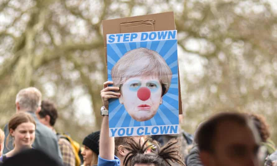 A protester holds a placard during the Put It To The People March in London on 23 March.