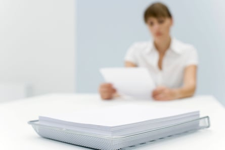 Stack of paper in metal tray, woman reading document in background