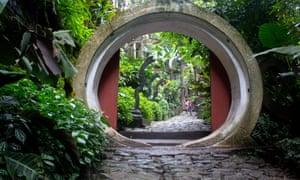 Circular tunnel-like sculpture amid verdant foliage in Las Pozas sculpture garden, Mexico