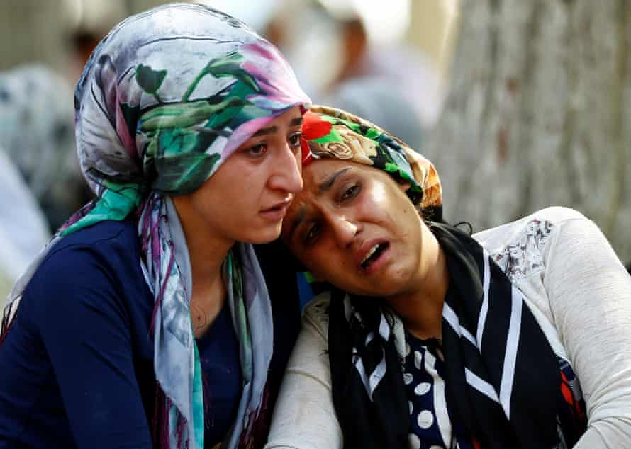 Women mourn as they wait in front of a hospital morgue