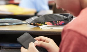 A young person using a mobile phone in class