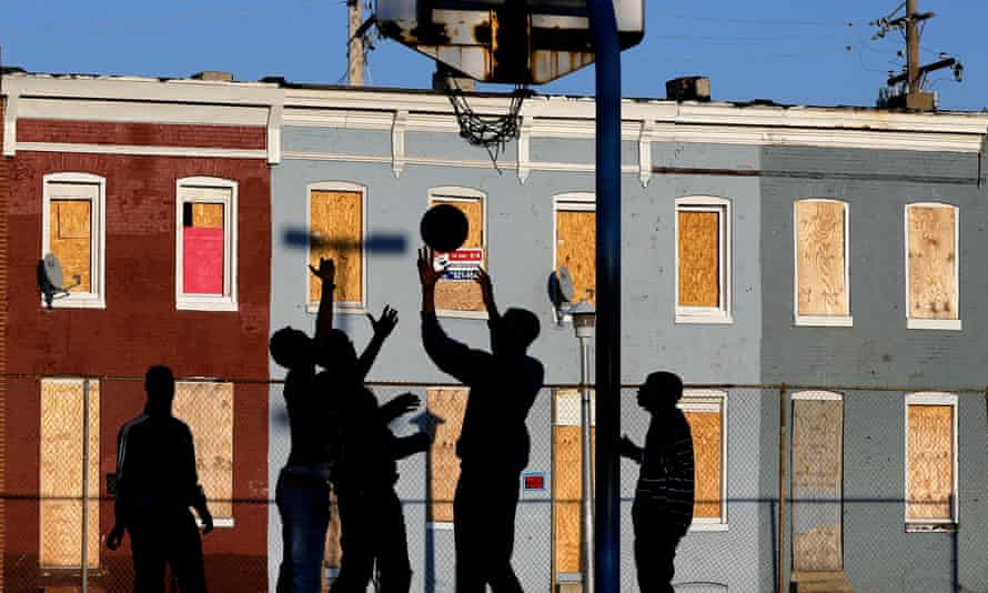 Children play basketball at a park near blighted row houses in Baltimore, Monday, April 1, 2013. Baltimore is far from the worst American city for poverty, but it faces all the problems of cities where vast numbers of the poor now live. The U.S. Census Bureau puts the number of Americans in poverty at levels not seen since the mid-1960s, while $85 billion in federal government spending cuts that began last month are expected to begin squeezing services for the poor nationwide. (AP Photo/Patrick Semansky)
