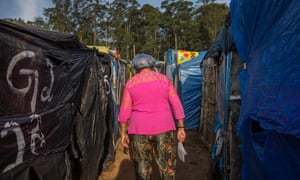 An occupant who works in the kitchen walks among the tents to get supplies