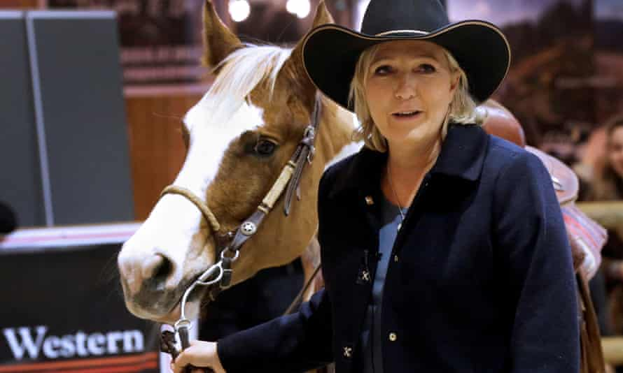 Marine Le Pen, French National Front political party leader, poses near a horse as she visits the Horse show in Villepinte, Paris.