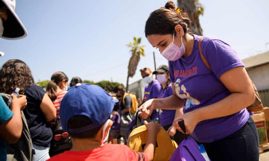Nurses and healthcare workers distribute backpacks to children during a back-to-school event in Los Angeles.