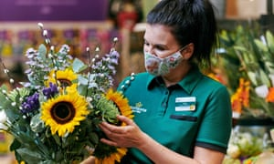 A woman in a green Morrisons uniform holding a bunch of flowers