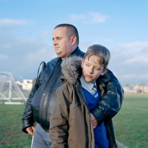 Man wraps arm around young boy in school uniform