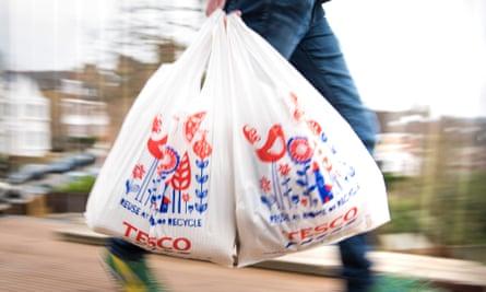 A shopper carrying Tesco bags