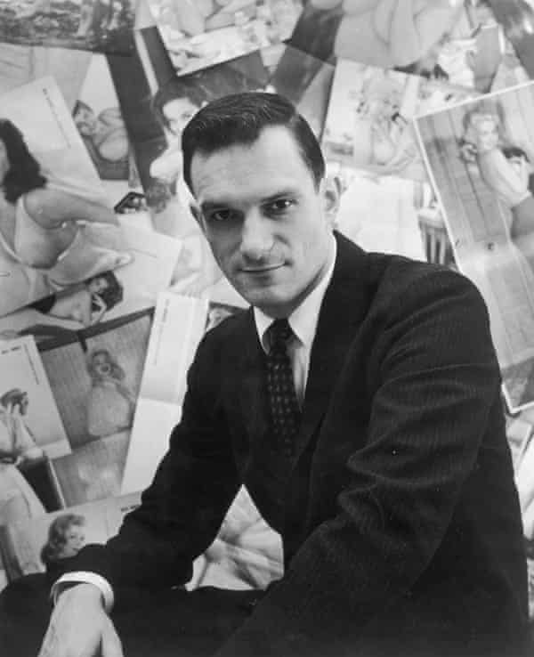 Portrait of American publisher Hugh Hefner sitting in front of a wall collage of female centerfolds from his men's magazine 'Playboy'