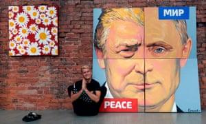 Alexey Sergienko poses next to his artwork depicting Donald Trump and Vladimir Putin.