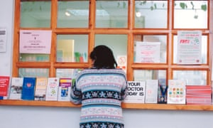 A female patient at a GP surgery reception desk.
