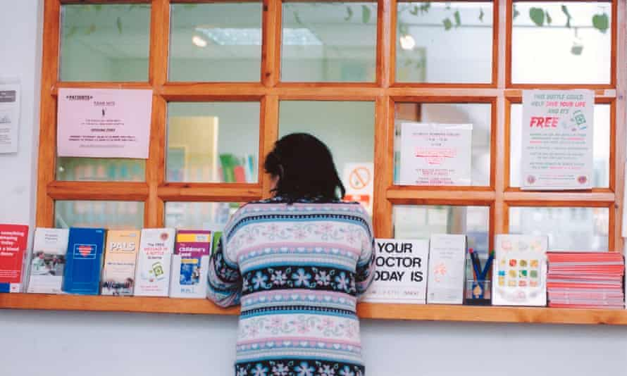 A woman waits at a GP surgery's reception desk.