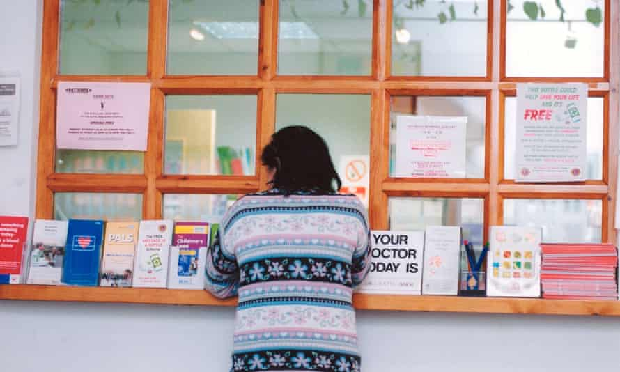 A patient at a GP surgery reception desk in Berkshire. NHS England insisted the patient data requested was not confidential or sensitive.