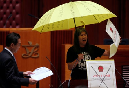 Leung Kwok-hung holds an umbrella while taking his oath at the legislative council.