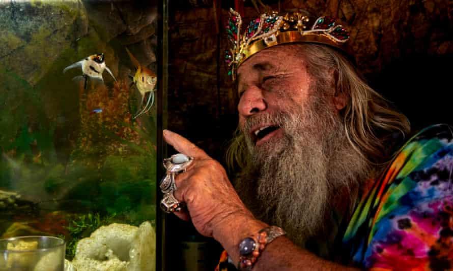 Garth wearing a bright tie-dye T-shirt, a crown and costume jewellery, pointing at fish in a tank