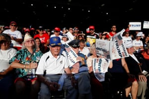 People listen to Trump speak at a campaign rally