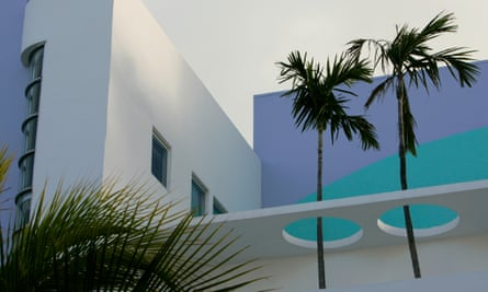 Palm trees poke through holes on the rooftop of a building designed in the art deco style, Miami Beach, Florida