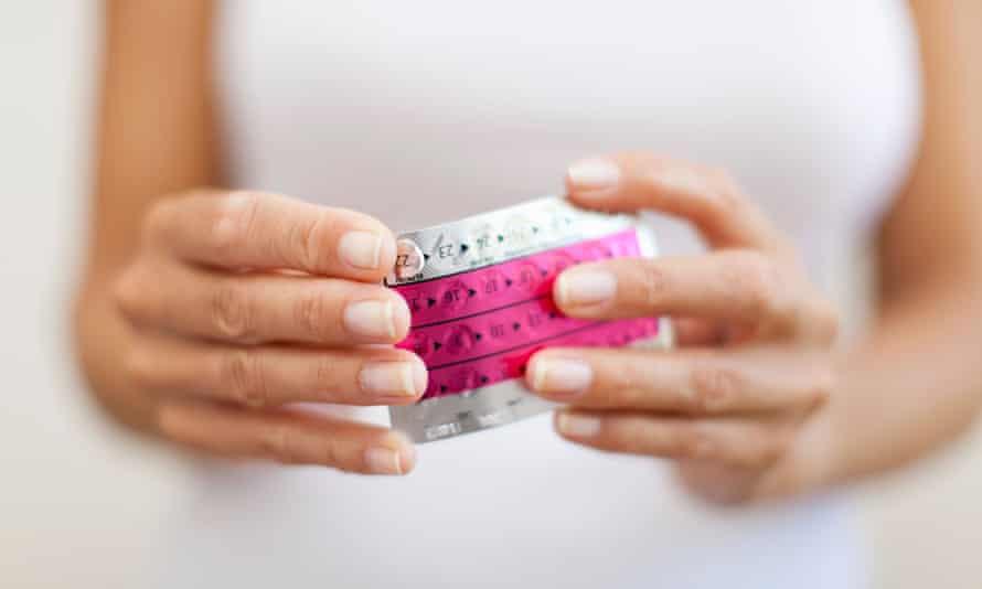 Woman's hand holding birth control pills,
