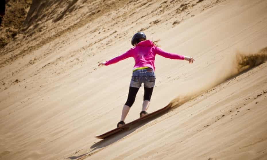 Sandboarding woman at Tottori Sand Dunes in Tottori City, Tottori Prefecture, Japan.