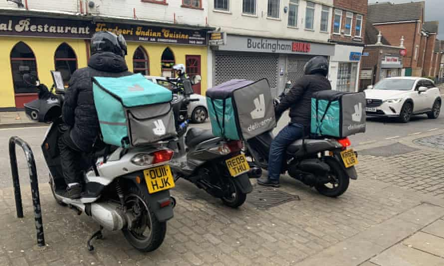 Deliveroo drivers on mopeds wait outside an Indian takeaway in Aylesbury, Buckinghamshire.