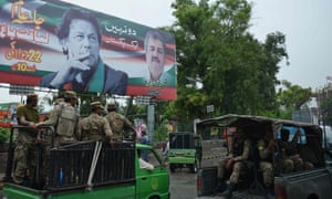 Pakistani soldiers in Rawalpindi patrol on a street beside a billboard featuring an image of Pakistani cricketer turned politician Imran Khan.