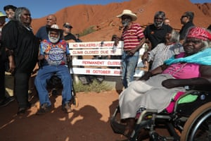 Traditional owners gather around the base of the Uluru climb after it was permanently closed on Friday evening.
