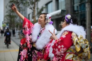 Women wearing kimonos take a selfie.