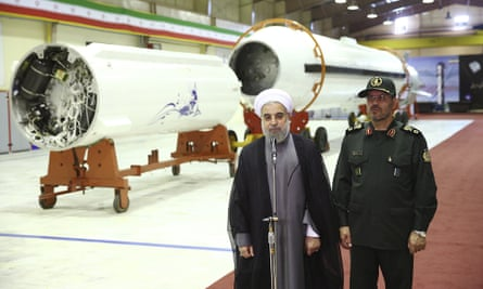 In an official photo released on Saturday, Iran's president Hassan Rouhani, left, briefs the media after unveiling the surface-to-surface Fateh-313, or Conqueror, missile.