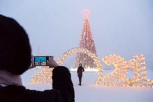 People pose for photos in front of an illuminated Christmas tree and 2021 sign
