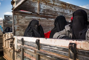Women who fled heavy fighting in the city of Baghuz sit in trucks taking them to a refugee camp for suspected Isis families
