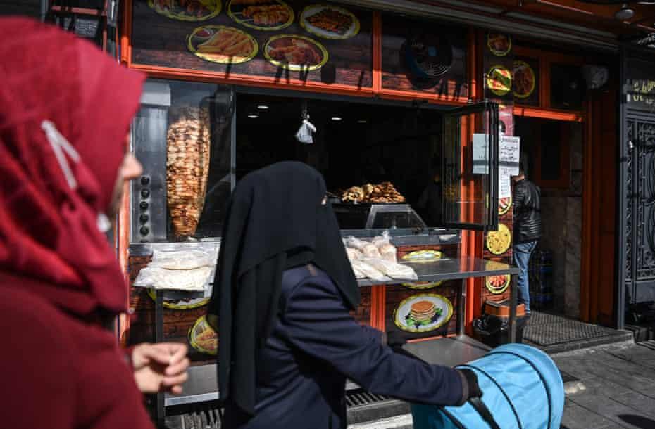 Syrian families outside a Syrian grill shop on Inonu street in Gaziantep, Turkey.
