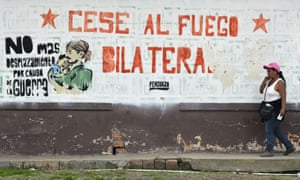 A woman walks past a mural in El Palo, Colombia, calling for a bilateral ceasefire.