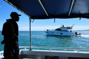 A crew member of police boat Veiqaravi watches a pleasure craft motor past in Nadi Bay