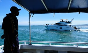 Crew member of Police boat Veiqaravi, watches a pleasure craft motor past in Nadi Bay