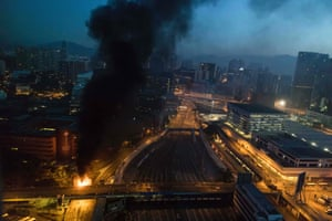 Smoke billows from a fire next to Hong Kong Polytechnic University, near an entrance to the besieged campus. Tensions soared after protesters threw Molotov cocktails to fend off a police advance