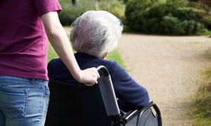 Woman pushing older woman in wheelchair