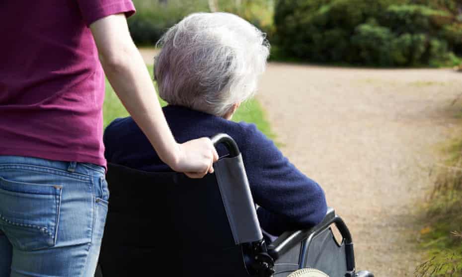 Daughter pushing elderly mother in wheelchair