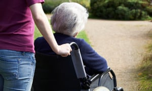 Woman pushing an older woman in a wheelchair.