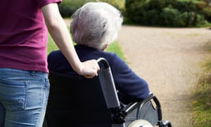 An elderly lady being pushed in a wheelchair