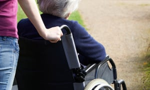 A woman pushing her mother in a wheelchair.