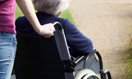 Female carer pushing elderly woman in a wheelchair
