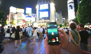 Big in Japan … people play Pokémon Go on their smartphones in Shibuya district, Tokyo.