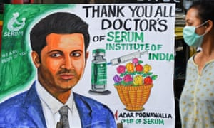 A woman walks through a painting welcoming the Coved 19 vaccination program with a picture of Adar Poonawala