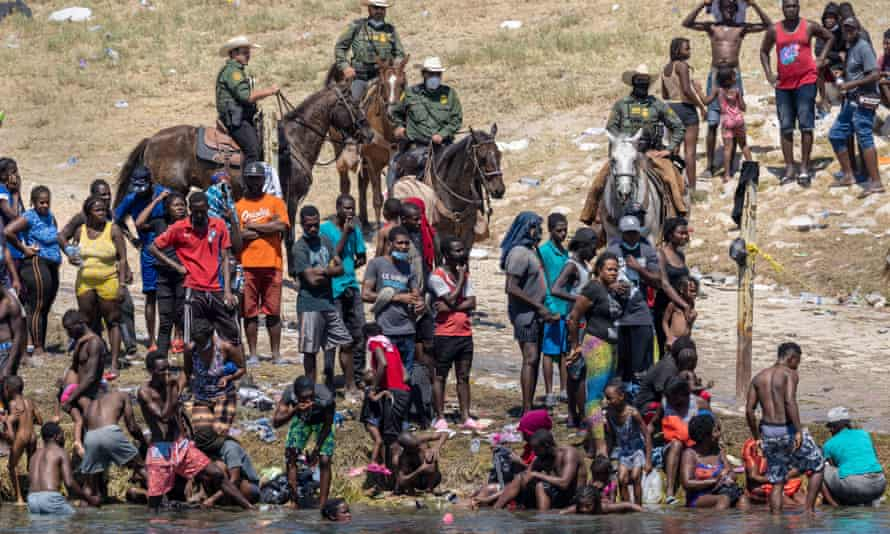 Mounted US border patrol agents watch Haitian immigrants on the bank of the Rio Grande in Del Rio, Texas, on Monday.