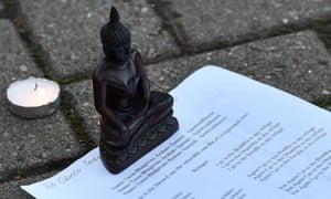 A statue of the Buddha is set on a paper with devotional Buddhist scripture in front of the floral tributes gathered outside the King Power.