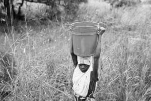 Ajida Patricio, 14, walks home with water in Mococorene, Nampula province