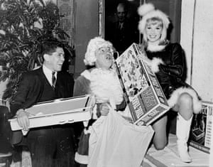 Former middleweight champ Rocky Graziano lets his beard drop and exposes his iron jaw at Leone's Restaurant where he, middleweight boxer Chico Vejar and TV actress Nina Paige help pack Christmas toys for disabled children