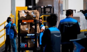 An Amazon delivery driver pushes a cart of groceries to load into a vehicle outside of a distribution facility on 2 February 2021 in Redondo Beach, California